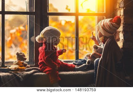 happy children brother and sister looking through the windows in the fall