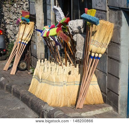 Street Retail Outlet selling traditional Household cleaning Items large Heap of Brooms and Besoms Mops Swobs variety of Brushes for cleaning Istanbul City Turkey