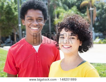 Laughing caucasian girl with african american boyfriend outdoor in the city in the summer