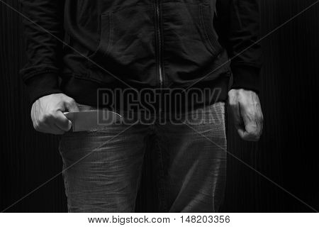 Closeup Of A Young Man Hand, Holding A Knife, About To Attack, Over Black Background. Representing T