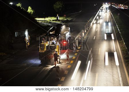 Wallau, Germany - September 16, 2016: High angle view of construction site on German highway A66 at night some workers in the foreground - long exposure