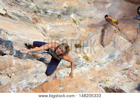 Beautiful Blond female Climber hanging on vertical Rock Wall her male Partner watching and belaying downstairs
