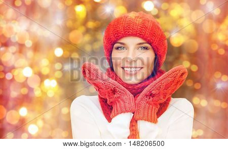 winter, people, christmas and holidays concept - happy smiling woman in hat, muffler and mittens over lights background