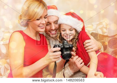 family, christmas, x-mas, winter, happiness and people concept - smiling family in santa helper hats looking at pictures