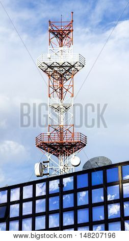 Antena on the building that reflects sky and clouds