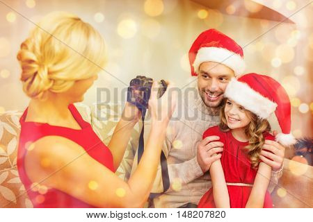 family, christmas, x-mas, winter, happiness and people concept - mother taking picture of smiling father and daughter in santa helper hats