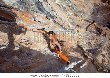 Top View of Rock Climber on orange Vertical Wall naked Torso looking up while other group of people staying far below