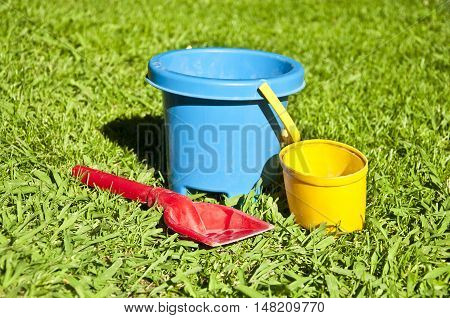 Kid toys: buckets and shovel on the grass