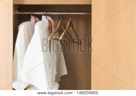 White bathrobe with hanger in wardrobe at hotel room