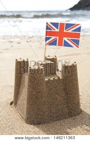 Sandcastle On Beach With Union Jack Flag