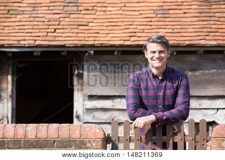Portrait Of Farmer Looking Over Wall Of Farm Building