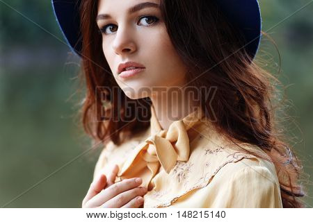 Outdoor closeup fashion portrait of glamour sensual young stylish lady wearing trendy hat. Autumn woman. Girl portrait. Fashion woman with curly hair and floppy hat. Closeup portrait of young beautiful brunette girl with brown eyes. Looking at camera