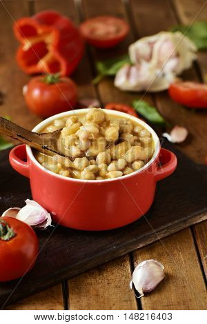 an earthenware casserole with potaje de garbanzos, a spanish chickpeas stew, and some vegetables to prepare it such as tomato, red pepper or garlics on a rustic wooden table