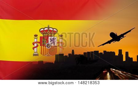 Travel and transport concept with skyline silhouette highway traffic and airplane at sunset merged with real fabric flag of Spain