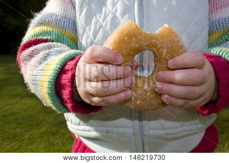 Young girl eating ring donut. Sticky fingers.