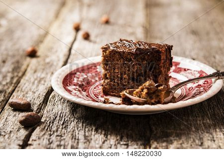 Chocolate cake. Piece of Chocolate hazelnut cake, topped with melted chocolate on a vintage plate in a rustic style on the rough wooden background
