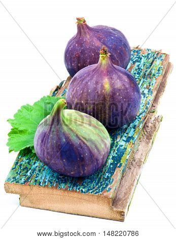 Three Perfect Ripe Fig on Cracked Wooden Planch isolated on White background