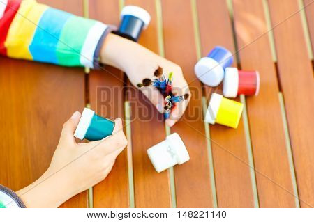 Closeup of child's hands with lots of brushes and colorful watercolors. Kid preparing stationary and student stuff. Back to school concept