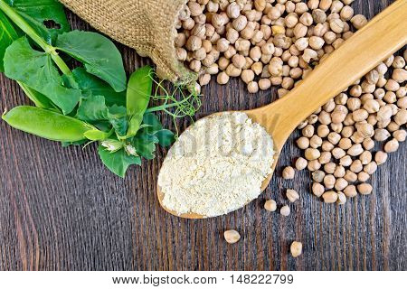 Flour chickpeas in spoonful, chick-peas in a sack and fresh pea pods on a background of wooden boards top