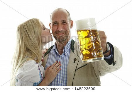 Woman in Dirndl and Man in traditional bavarian Oktoberfest leather Cloting cheering with a beer mug