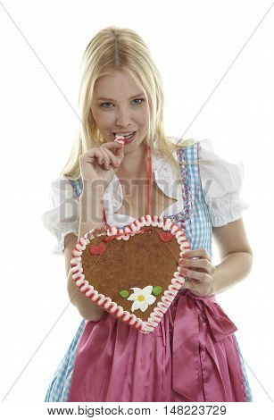 Woman bites in an empty Oktoberfest Gingerbread heart with copy space