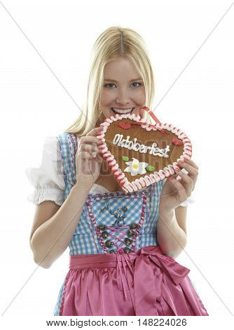 Woman bites in a German Oktoberfest Gingerbread heart