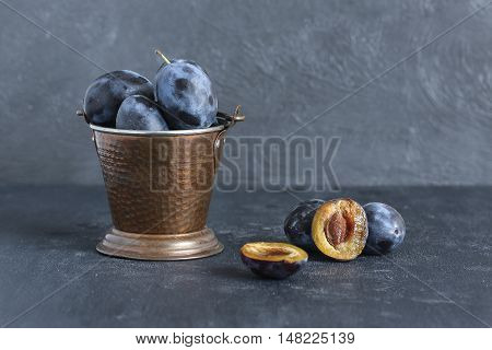 Bucket of plums and half of the plum with seed on gray background