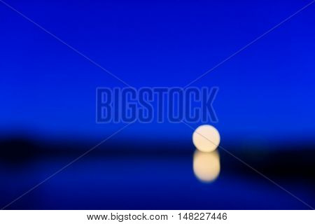 Full moon rising over lake in September on clear cloudless night in Western Finland.