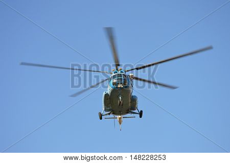 Middle size helicopter flying in a clear blue sky