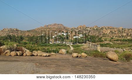Granite boulder and granite mountains in Hampi India. Travel destination in Karnataka. Unique landscape. Ruin of an old bridge.