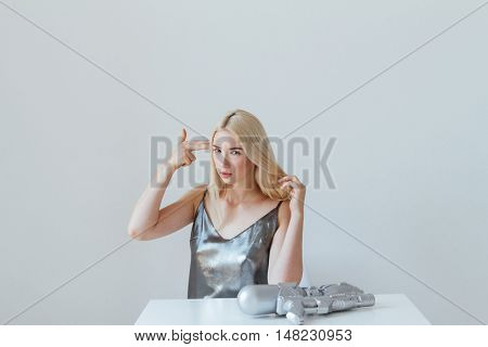 Young beautiful fashion woman holding her hand like a gun near head and looking at camera isolated in the grey background
