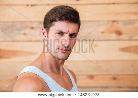 Closeup portrait of a serious man looking at camera isolated on a wooden background