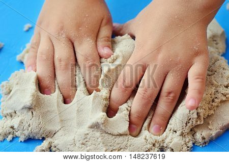 Child playing with kinetic sand. Hands of the child in the sand close up on a bright background