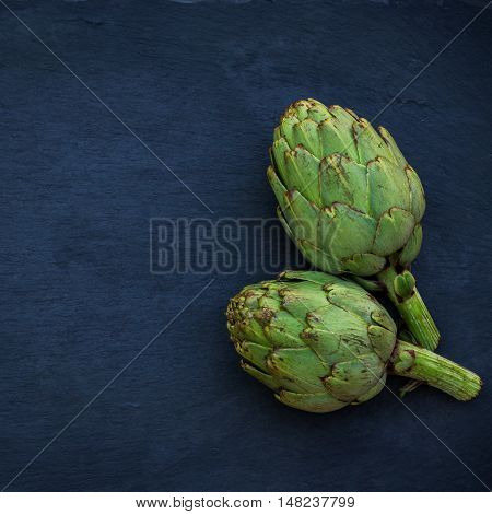 Organic fresh artichokes on a grunge moody background. Selective focus, top view, copy space, overhead flat lay