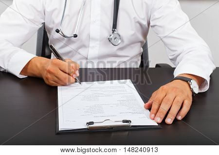 Picture of a doctor's hand signing on the medical report