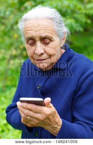 Picture of an old woman holding a smartphone in her hands