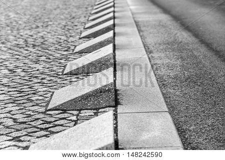 Triangular fences stone border and asphalt road.