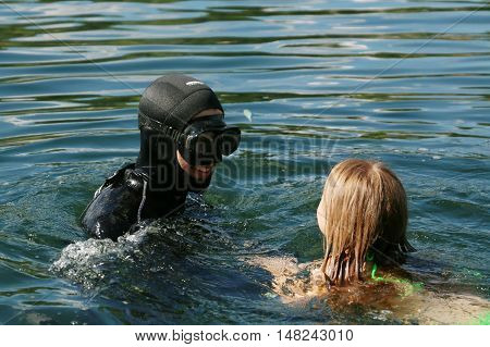 Diver plays with a child in the water