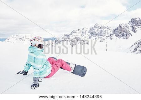 Female snowboarder wearing colorful helmet, blue jacket, grey gloves and pink pants sitting against snowy mountains and preparing for ride - snowboarding concept