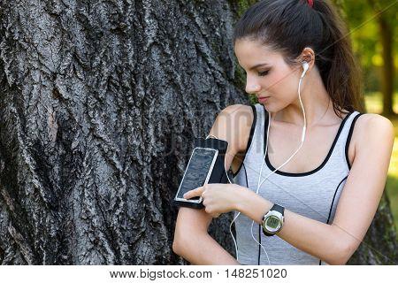 Female Runner Settings Smart Phone In Armband