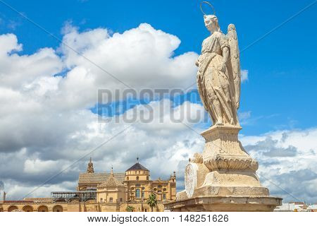 San Rafael Archangel statue on the popular Roman Bridge in Cordoba with behind the Cathedral of the Andalusian city Spain.