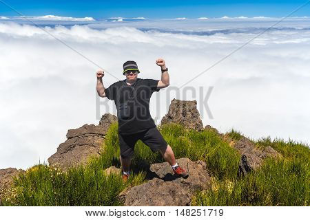 Obese man standing at top of the mountain over the clouds. If you want you can achieve even hard and tough goal. All you need is desire and strong will. Even fat people can achieve their own tops.