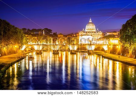 Rome skyline at night with San Pietro basilica or Saint Peter cathedral with Sant'Angelo bridge reflected on Tevere river illuminated by city lights of Roma in Italy.