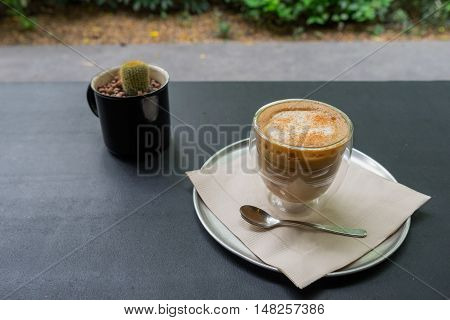 hot fresh coffee in see through glass with silver spoon and small green cactus plant on black table at coffee time / hot fresh coffee