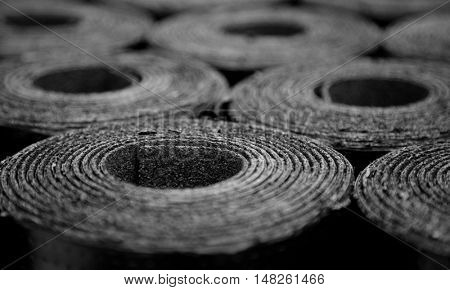 Closeup of Rolls of new black roofing felt or bitumen. Selective focus