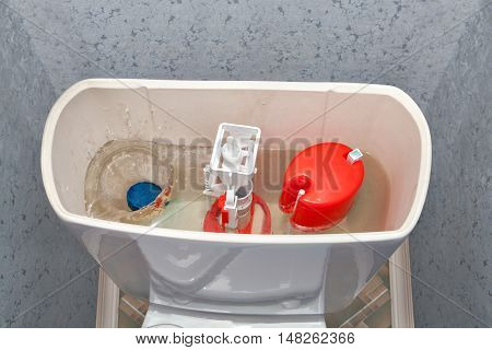 Blue cleaning water-soluble tablet falls into the water drain the toilet tank.