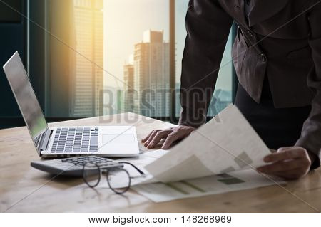Business woman standing hand holding document finacial report wokring with laptop computer. selective focus on glasses.