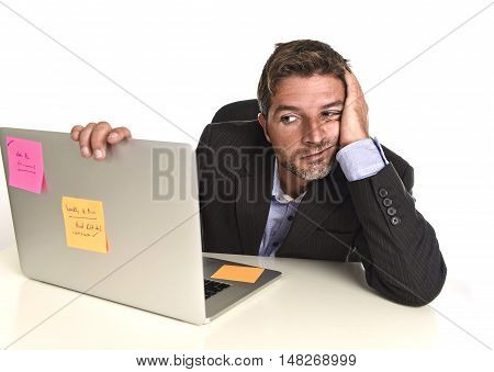 young attractive businessman looking worried face expression suffering stress at office laptop computer having work problem sitting on desk frustrated and bored isolated on white background