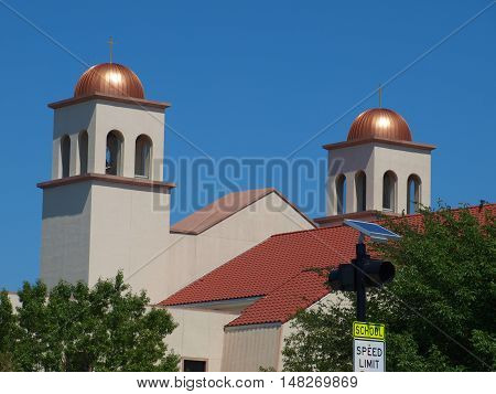 The twin bell towers of a large Spanish Mission type architecture Catholic church coated the domes so that they will never turn green. The main dome over the cruciform and the apse dome are also coated but much larger in scale.