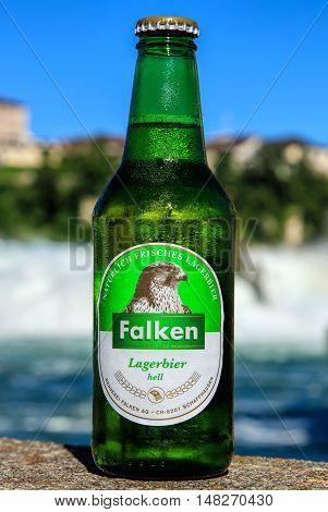 Neuhausen am Rheinfall, Switzerland - 22 June, 2016: a bottle of Falken bier covered by drops of water, the Rhine Falls in the background. Falken bier has been brewed by the Falken brewery in the Swiss city of Schaffhausen since 1799.